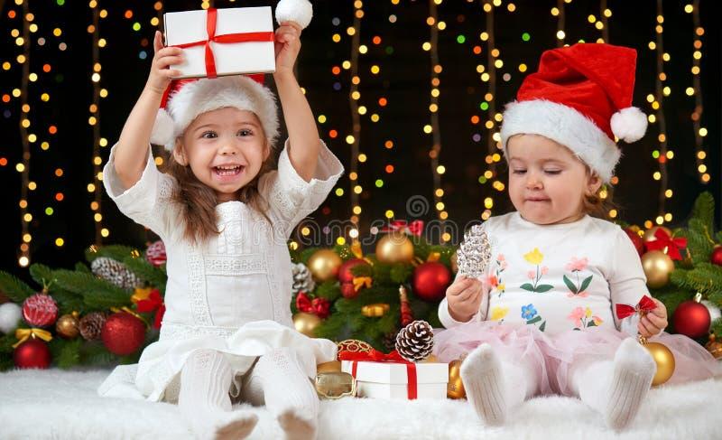 Portrait de fille d'enfant en décoration de Noël, émotions heureuses, concept de vacances d'hiver, fond foncé avec l'illumination photo libre de droits