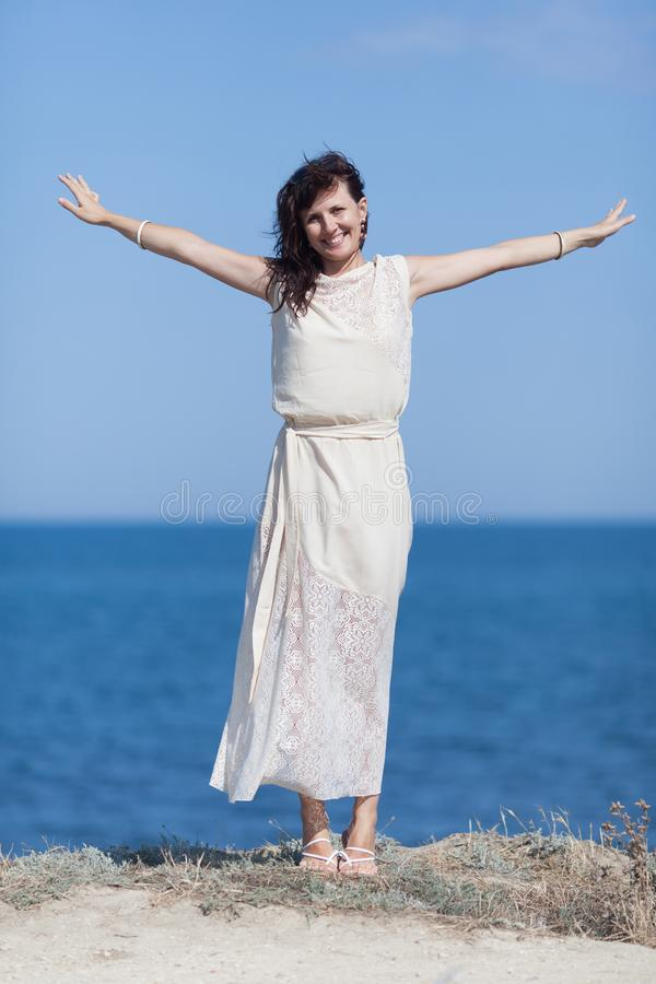 Portrait de fille dans la robe sans manche blanche avec l'outstretche de bras photo libre de droits