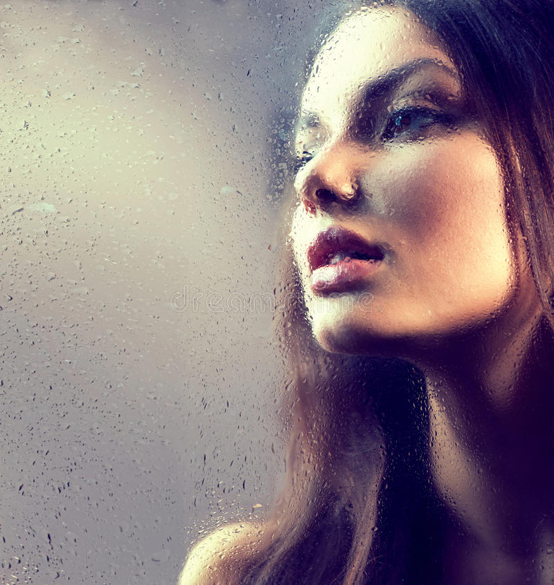 Portrait de fille de beauté derrière le verre humide photo stock
