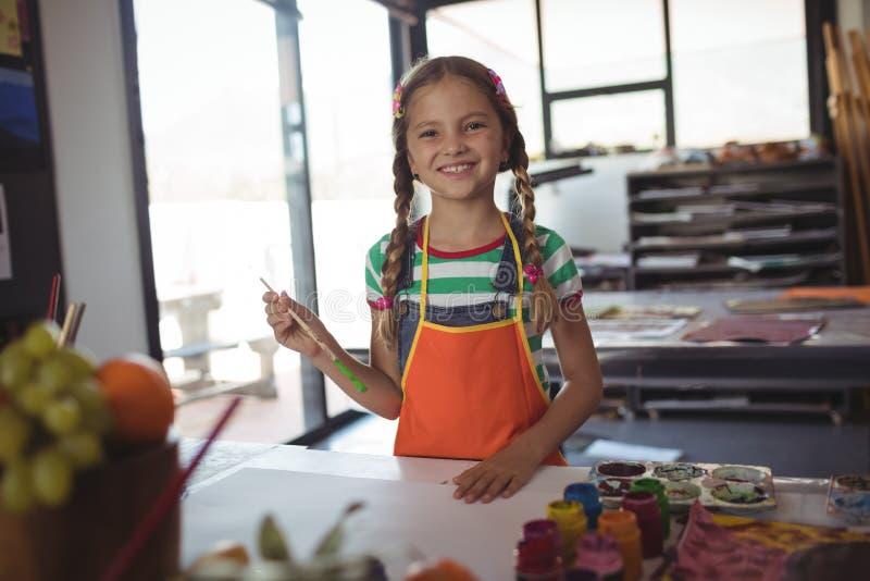 Portrait de fille de sourire à la classe de peinture photo stock