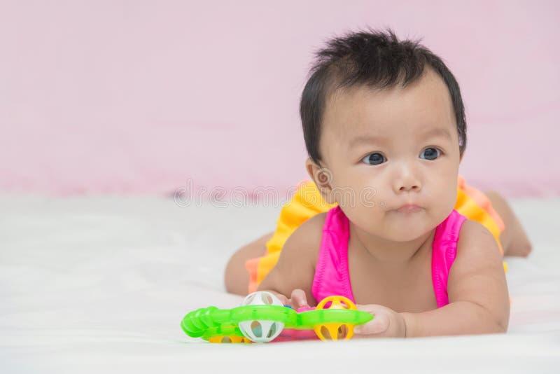 Portrait de fille de sourire de bébé mignon sur le lit avec le jouet photos stock