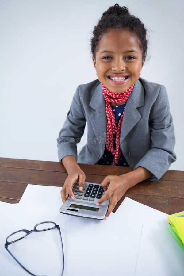Portrait de fille de sourire feignant comme femme d'affaires à l'aide de la calculatrice images libres de droits
