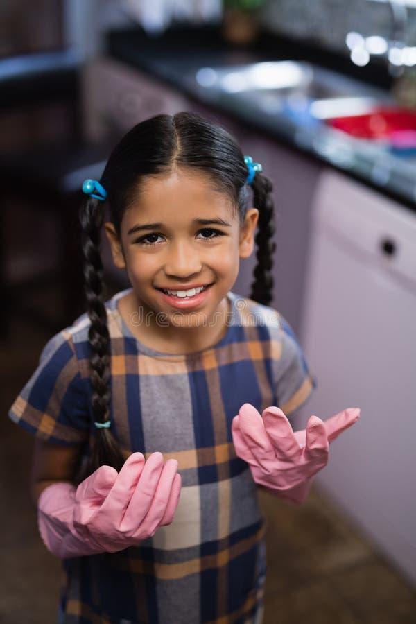 Portrait de fille de sourire portant les gants roses dans la cuisine image libre de droits