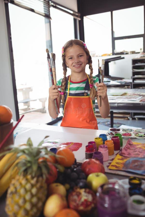 Portrait de fille de sourire tenant des pinceaux par le bureau photo stock