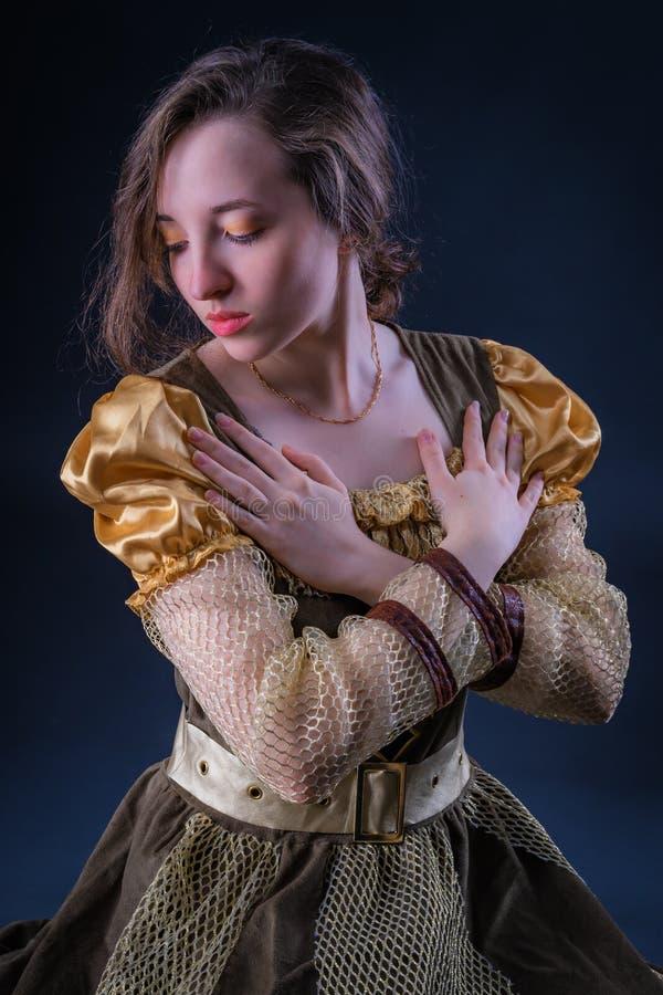 Portrait de fille expressive gracieuse avec les yeux abaissés dans la robe de cru images libres de droits