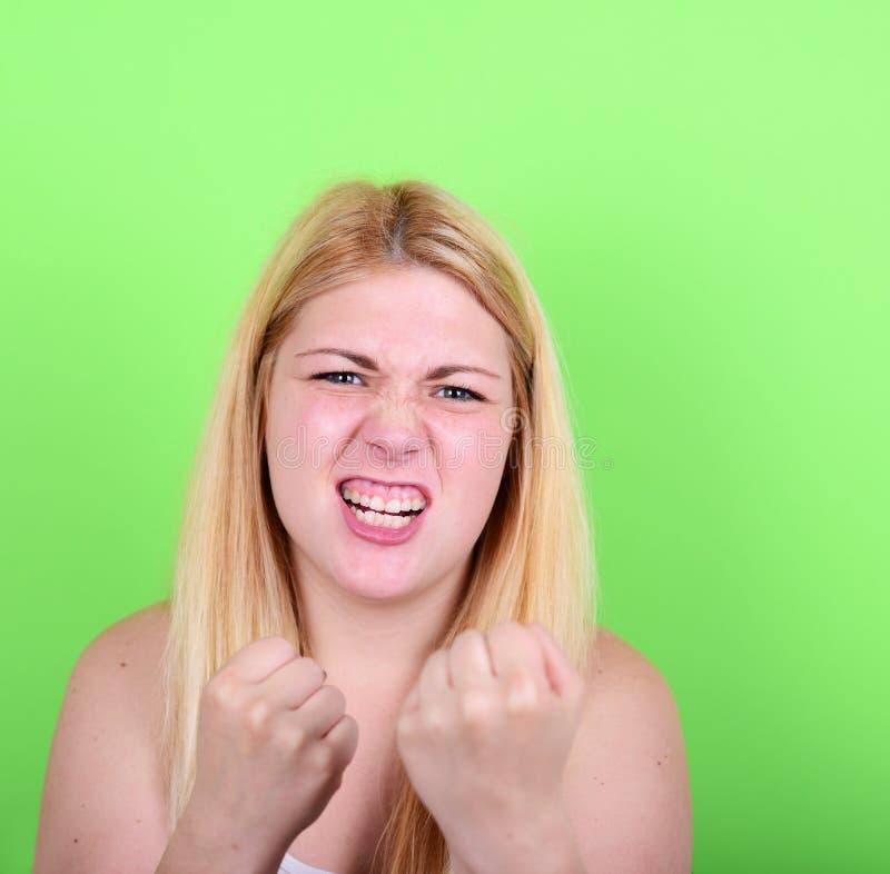 Portrait de fille fâchée tenant des poings sur le fond vert photos stock