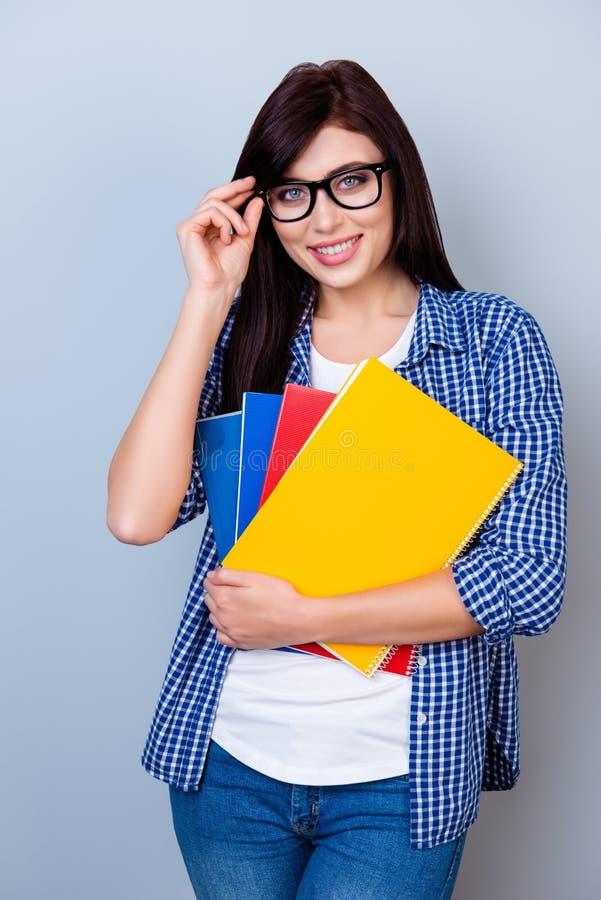 Portrait de fille heureuse d'étudiant en verres tenant des carnets dans h photographie stock