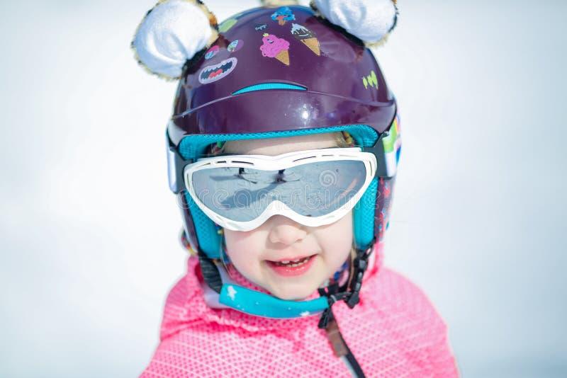 Portrait de fille heureuse mignonne de skieur dans le casque et de lunettes dans une station de sports d'hiver d'hiver photographie stock libre de droits