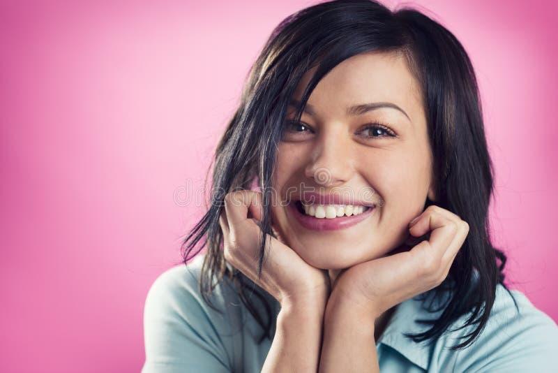 Portrait de fille joyeuse de sourire avec des mains au menton photo libre de droits