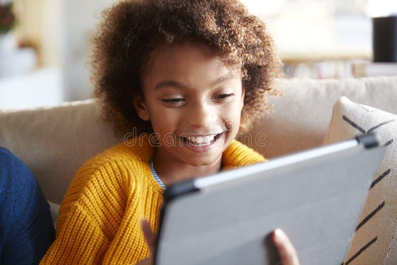 Portrait de fille de la préadolescence regardant l'écran de tablette riant, fin, foyer sélectif photographie stock