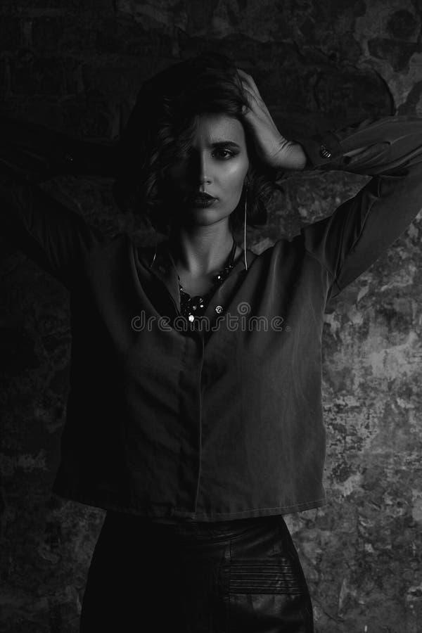 Portrait de fille luxueuse de brune avec des cheveux de vague posant avec la lumière de contraste Tonalité noire et blanche photographie stock