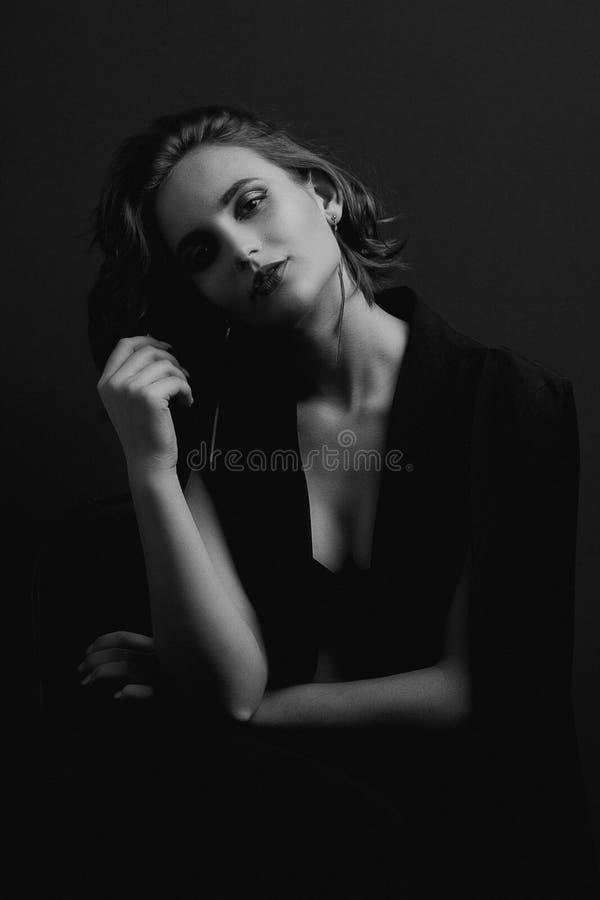 Portrait de fille merveilleuse de brune avec des cheveux de vague posant avec la lumière de contraste Tonalité noire et blanche photographie stock