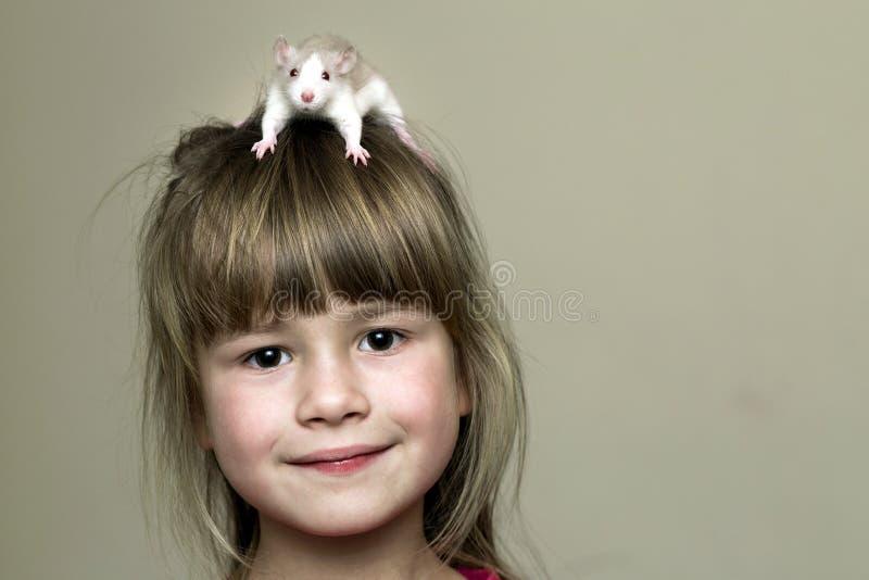 Portrait de fille mignonne drôle de sourire heureuse d'enfant avec le hamster blanc de souris d'animal familier sur la tête sur l photos stock