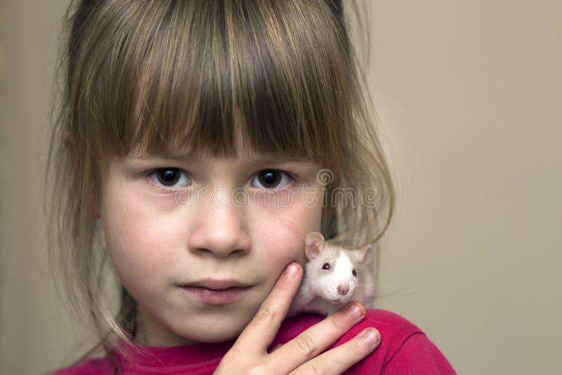 Portrait de fille mignonne de sourire heureuse d'enfant avec le hamster blanc de souris d'animal familier sur le fond clair de l' images stock