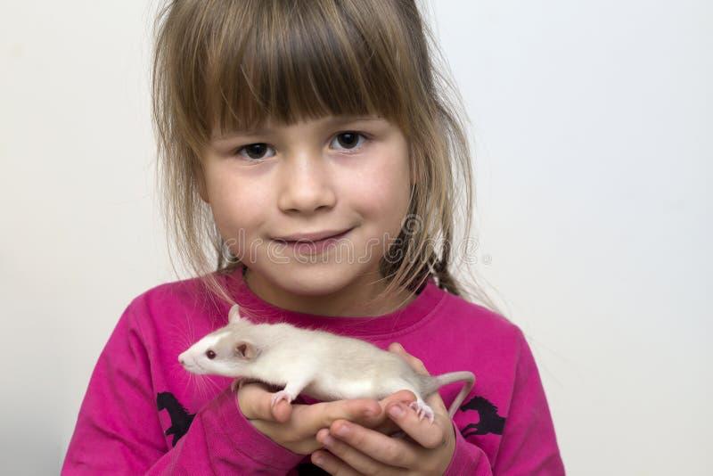 Portrait de fille mignonne de sourire heureuse d'enfant avec le hamster blanc de souris d'animal familier sur le fond clair de l' image libre de droits