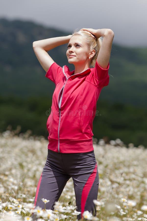Portrait de fille mince dans les vêtements de sport au champ de camomille photographie stock