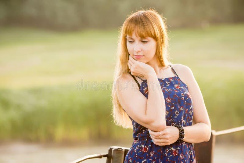 Portrait de fille modeste songeuse sur le fond vert brouillé image libre de droits