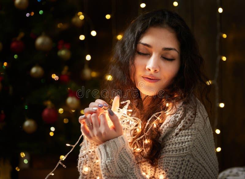 Portrait de fille rêvante avec la poignée de lumières de Noël, yeux fermés, habillés dans le chandail blanc, fond en bois foncé,  photos libres de droits