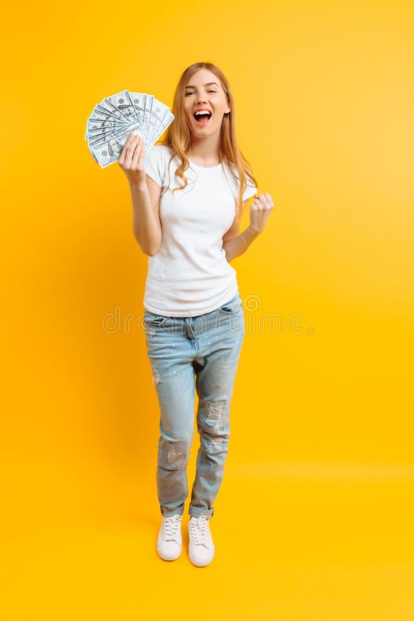 Portrait de fille satisfaite heureuse avec un groupe de billets de banque et de victoire de célébration et le succès sur le fond  photo stock