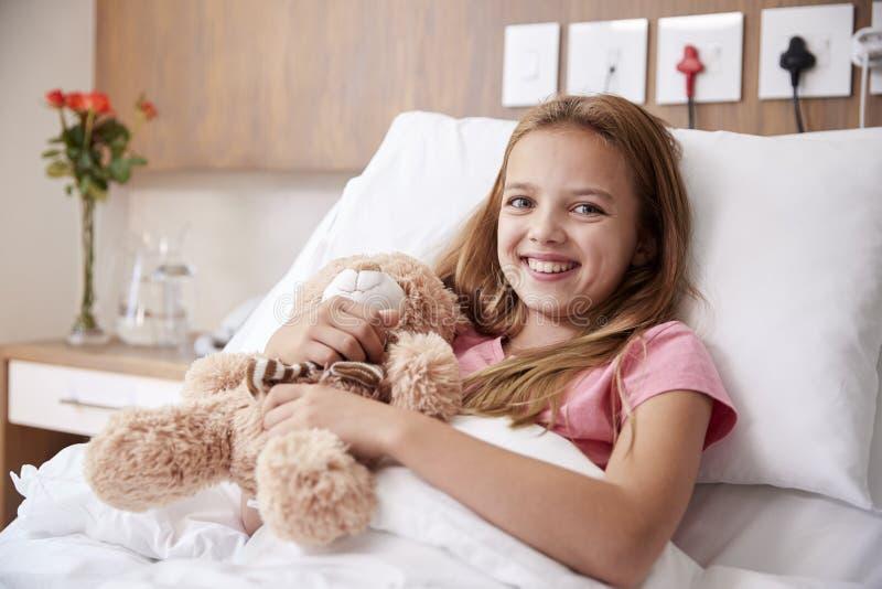 Portrait de fille se situant dans le lit dans l'hôpital Ward Hugging Teddy Bear photos libres de droits