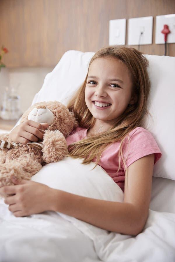 Portrait de fille se situant dans le lit dans l'hôpital Ward Hugging Teddy Bear photographie stock