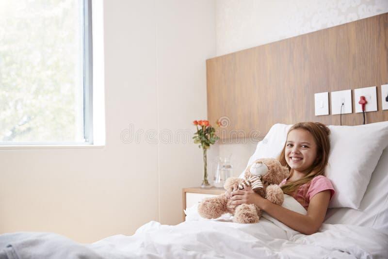 Portrait de fille se situant dans le lit dans l'hôpital Ward Hugging Teddy Bear photo stock