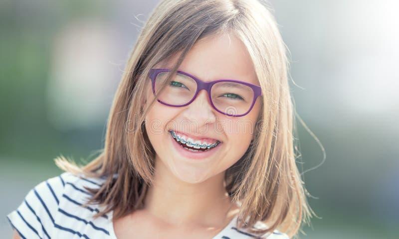 Portrait de fille de sourire heureuse avec des bagues dentaires et des verres photos stock
