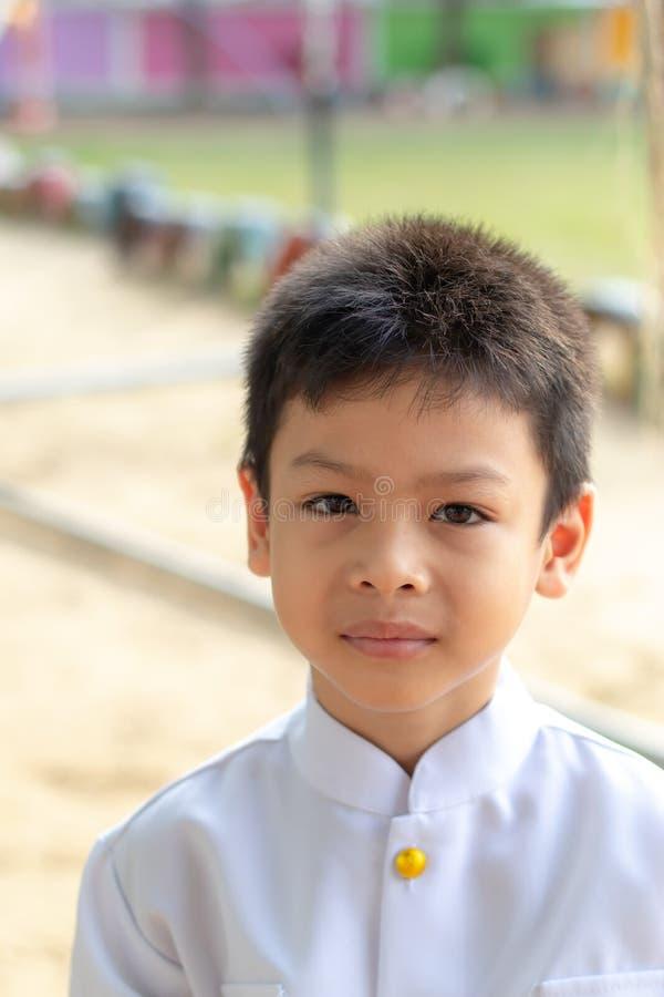 Portrait de garçon asiatique utilisant une chemise blanche dans l'herbe photographie stock libre de droits