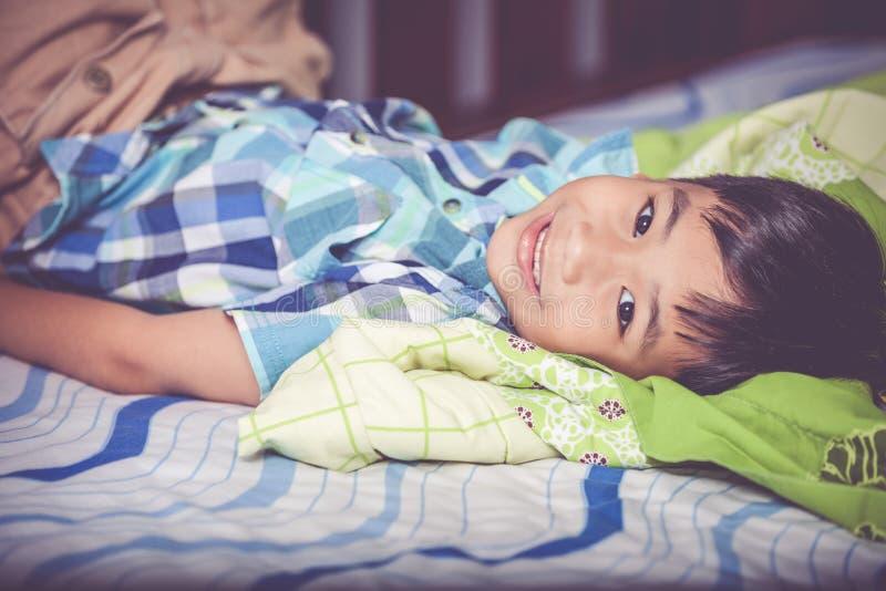 Portrait de garçon beau se trouvant sur le lit dans la chambre à coucher Ton e de vintage photographie stock libre de droits