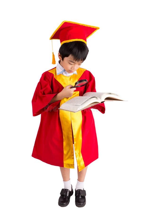 Portrait de garçon curieux dans l'obtention du diplôme rouge d'enfant de robe avec Mortarbo photo libre de droits