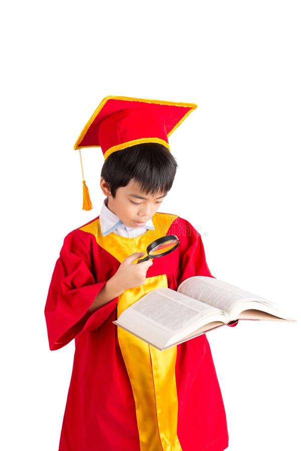 Portrait de garçon curieux dans l'obtention du diplôme rouge d'enfant de robe avec Mortarbo images libres de droits