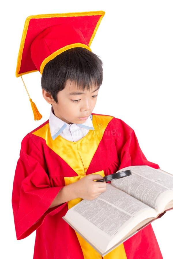 Portrait de garçon curieux dans l'obtention du diplôme rouge d'enfant de robe avec Mortarbo image libre de droits