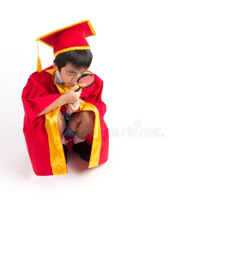 Portrait de garçon curieux dans l'obtention du diplôme rouge d'enfant de robe avec Mortarbo photographie stock libre de droits