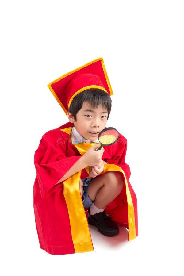 Portrait de garçon curieux dans l'obtention du diplôme rouge d'enfant de robe avec Mortarbo photo stock