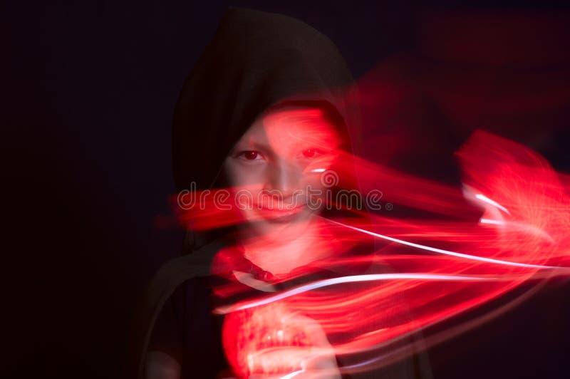 Portrait de garçon dans l'obscurité avec des effets de lumière rouge sur le fond noir photographie stock libre de droits
