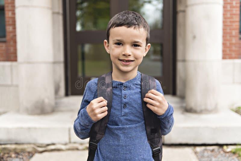 Portrait de garçon mignon avec le sac à dos en dehors d'école photographie stock libre de droits