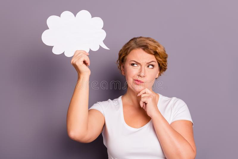 Portrait de gentille dame aux cheveux ondulés triste attirante dans le T-shirt blanc occasionnel tenant la création de pensée de  photos stock