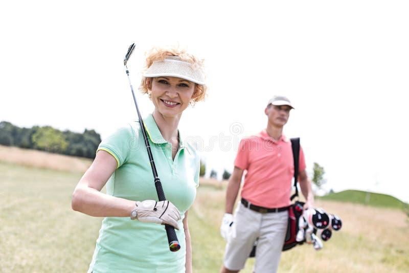 Portrait de golfeur féminin heureux avec l'ami se tenant à l'arrière-plan photographie stock libre de droits
