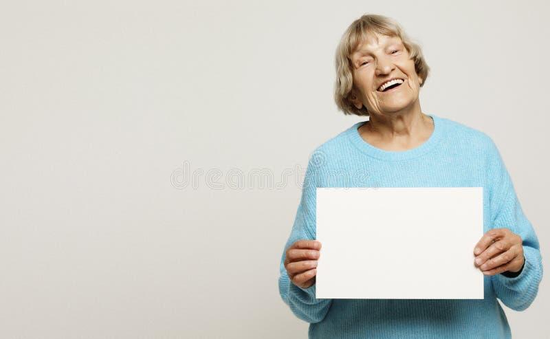 Portrait de grand-mère expressive belle dans d'intérieur bleu-clair, tir de studio, d'isolement sur le fond gris images stock