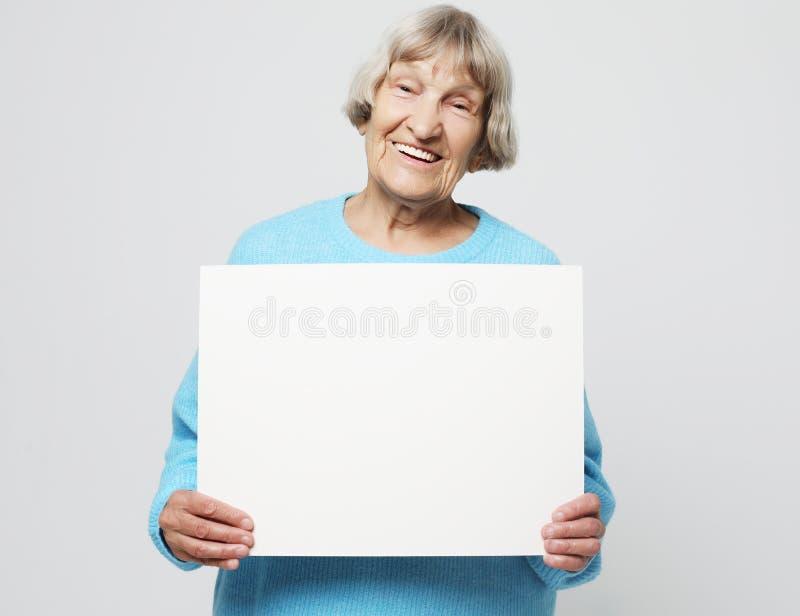 Portrait de grand-mère expressive belle dans le chandail bleu-clair D'intérieur, tir de studio, d'isolement sur le fond gris image stock