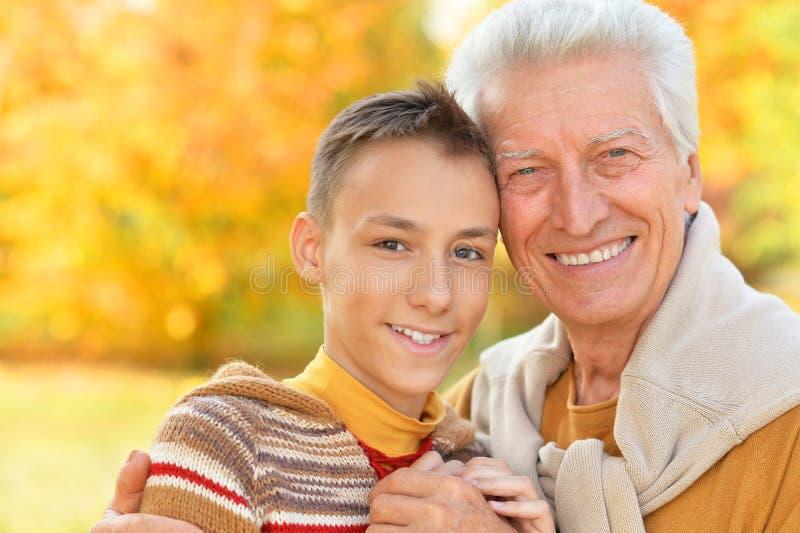 Portrait de grand-p?re et de petit-fils heureux en parc image stock
