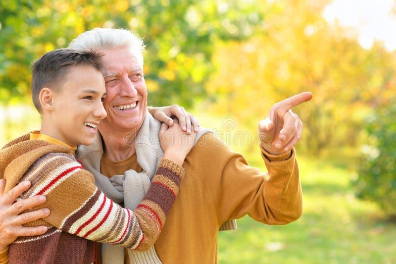 Portrait de grand-p?re et de petit-fils heureux en parc photo stock