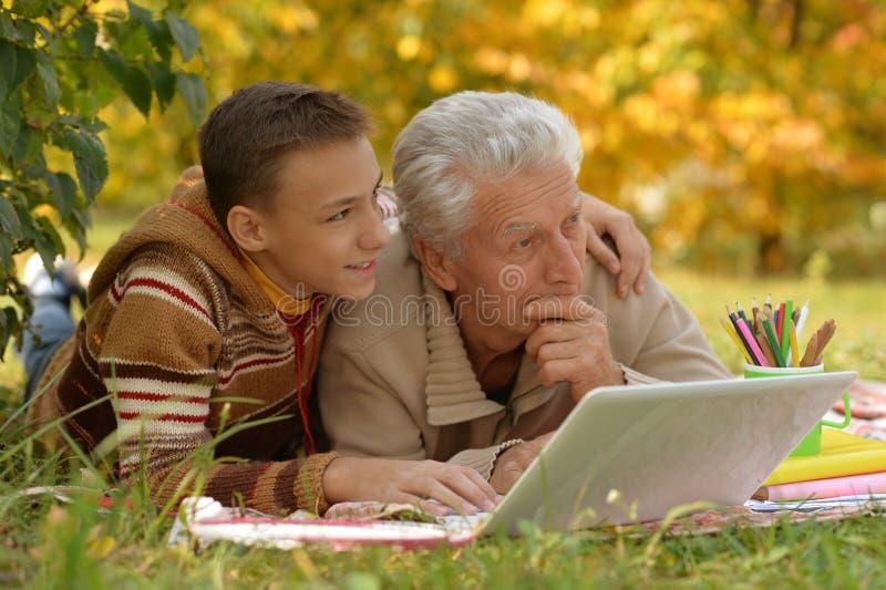 Portrait de grand-p?re et son petit-fils dessinant dehors image stock