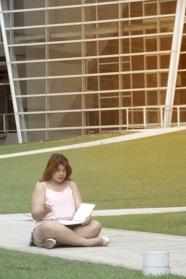 Portrait de grosses pose, participation et écriture de femme de joli visage souriant asiatique un livre photos libres de droits