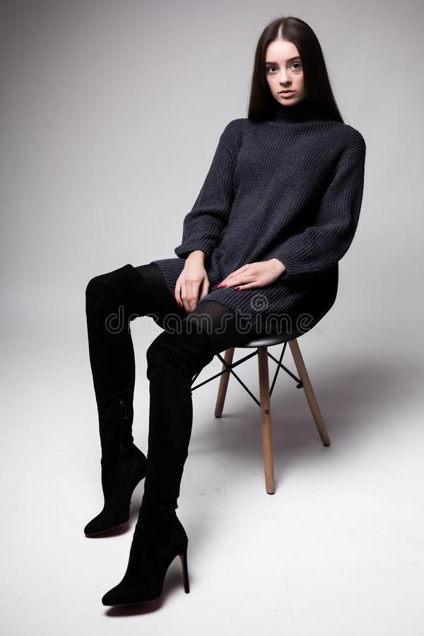 Portrait de haute couture de jeune sittung de femme élégante sur des vêtements de noir de chaise d'isolement sur le fond blanc images stock