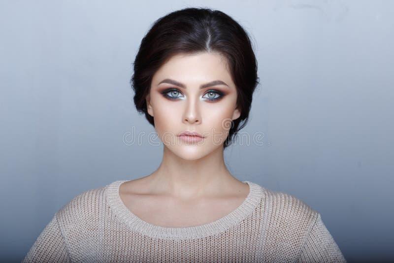 Portrait de Headshot de fille sensuelle de brune avec stup?fier les yeux verts, maquillage parfait, regardant la cam?ra Fond gris photos libres de droits