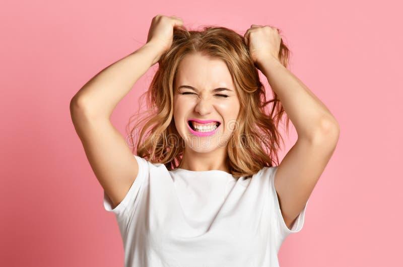 Portrait de hurlement de cri criard de plan rapproché de femme émotive sur le fond rose tirant les cheveux principaux photo stock
