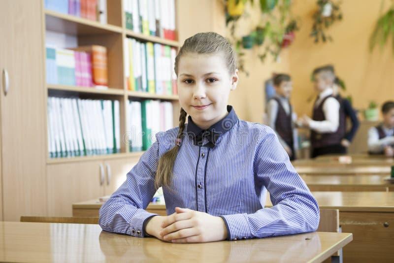 Portrait de jeune écolière souriant tout en se reposant au bureau avec des camarades de classe à l'arrière-plan image libre de droits