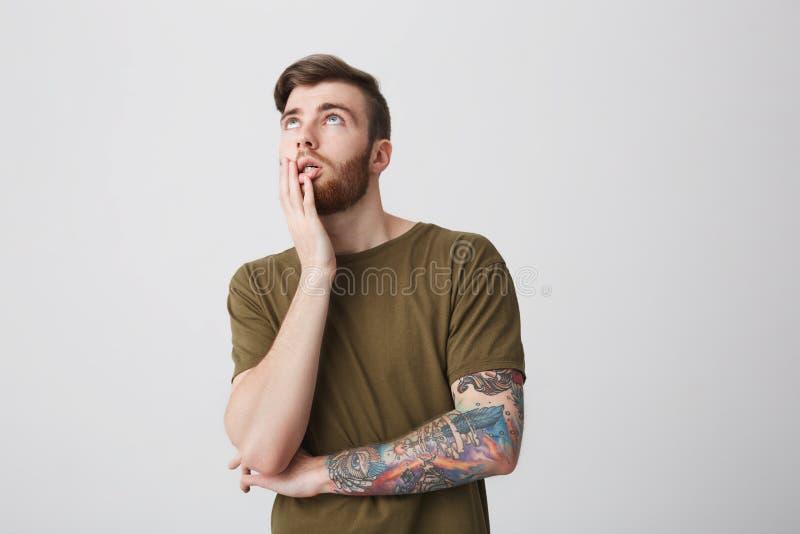 Portrait de jeune étudiant masculin beau barbu drôle avec les cheveux courts foncés et de tatouage sur le bras dans t coloré occa image stock