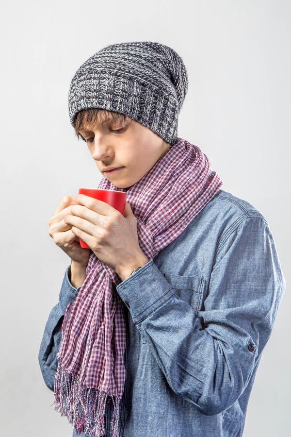 Portrait de jeune adolescent congelé mignon dans une écharpe et avec la tasse de thé image libre de droits